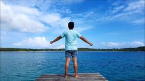 Un hombre que se coloca en el puente de madera del mar y los brazos abiertos, gritando para su lanzamiento almacen de video