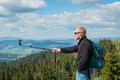 Un hombre que se coloca en el top de la alta colina con la cámara de la acción - fabricación del selfie, arriba en montañas natur Foto de archivo libre de regalías