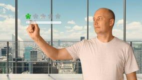 Un hombre que se coloca en una oficina moderna con las ventanas panorámicas fija un grado en una pantalla virtual Mantenga las es Fotografía de archivo libre de regalías