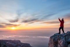 Un hombre en el top de la montaña con los brazos abiertos Imágenes de archivo libres de regalías
