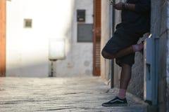 un hombre que se inclina contra la pared usando un teléfono móvil imagen de archivo