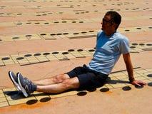 Un hombre que se sienta en la tierra con el fondo del modelo de la nota musical Foto de archivo libre de regalías