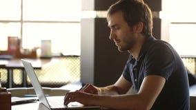 Un hombre que se sienta en un café y que trabaja en un ordenador portátil almacen de metraje de vídeo