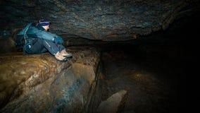 Un hombre que se sienta en una cueva. Imagen de archivo