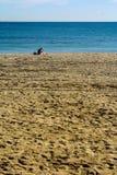 Un hombre que se sienta solamente en la playa imágenes de archivo libres de regalías