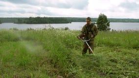 Un hombre que siega el condensador de ajuste de la hierba almacen de video