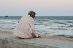 Un hombre que sienta y que mira el mar imagen de archivo libre de regalías