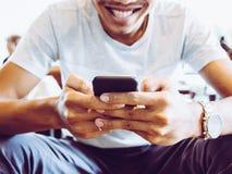 Un hombre que sonríe con su teléfono foto de archivo libre de regalías