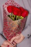 Un hombre que sostiene un ramo de rosas rojas imagen de archivo