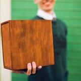Un hombre que sostiene una caja de madera Imagen de archivo libre de regalías