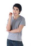 Un hombre que sostiene una manzana con feliz Foto de archivo