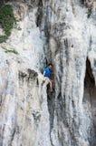 Un hombre que sube para arriba los acantilados escarpados de una piedra caliza Foto de archivo libre de regalías