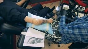 Un hombre que tatúa una mano prostética de una persona discapacitada almacen de video