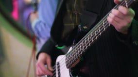 Un hombre que toca la guitarra baja con efecto luminoso metrajes