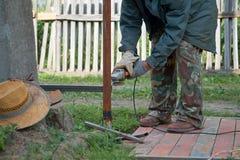 Un hombre que trabaja con la amoladora de ángulo en el patio trasero fotografía de archivo libre de regalías