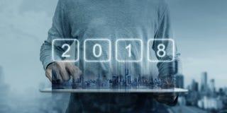 Un hombre que trabaja en la tableta digital con los edificios modernos de la ciudad y el holograma 2018 del Año Nuevo Desarrollo  Imagen de archivo