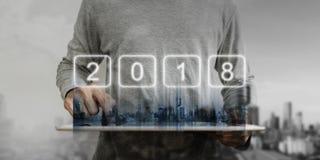 Un hombre que trabaja en la tableta digital con los edificios modernos de la ciudad y el holograma 2018 del Año Nuevo Desarrollo  imagen de archivo libre de regalías
