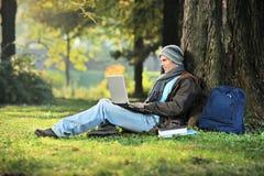 Un hombre que trabaja en una computadora portátil Fotografía de archivo