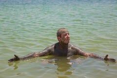 Un hombre que usa el fango médico, nadada en el mar muerto fotos de archivo