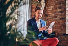 Un hombre que usa la tableta en un cuarto con el interior del desván foto de archivo libre de regalías
