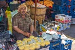 Un hombre que vende la mantequilla en mercado público Imagen de archivo libre de regalías