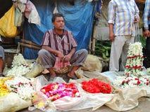 Un hombre que vende las flores en el mercado Foto de archivo libre de regalías