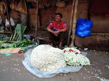 Un hombre que vende las flores en el mercado Fotos de archivo libres de regalías