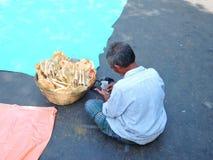 Un hombre que vende una cesta por completo de poppadoms o de papad Imagenes de archivo