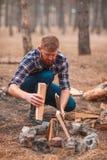 Un hombre recoge un fuego de un fuego en el bosque del otoño Imágenes de archivo libres de regalías