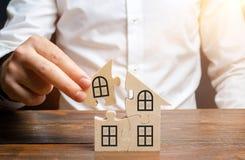 Un hombre recoge una casa de rompecabezas Construcción de su propio edificio residencial Préstamo de hipoteca, extensión residenc foto de archivo libre de regalías