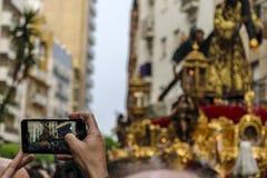 Un hombre registra con su teléfono móvil a la procesión de Jesús el Nazarene en Huelva, España fotos de archivo