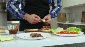 Un hombre regordete cocina las hamburguesas en casa en su cocina El individuo pone el queso dentro de una hamburguesa Forma de vi almacen de video