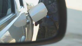 Un hombre rellena un coche de la gasolina almacen de metraje de vídeo
