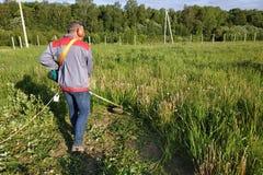 Un hombre rema la hierba con un condensador de ajuste del roble en el campo, en la yarda está el verano y el sol brilla fotos de archivo libres de regalías