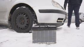 Un hombre repara un coche, arranque en frio en el invierno, batería débil, MES lento almacen de video
