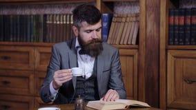 Un hombre respetable bebe el café de la mañana y lee un libro en la biblioteca Un hombre barbudo inteligente lee un libro metrajes