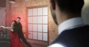 Un hombre rico es celoso de una mujer en un tango rojo del baile del vestido con un bailarín metrajes