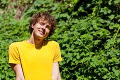 Un hombre rizado joven en un bosque foto de archivo