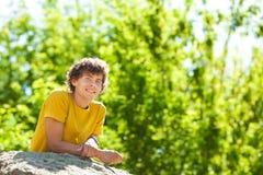 Un hombre rizado joven en un bosque imagen de archivo libre de regalías