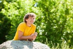 Un hombre rizado joven en un bosque imágenes de archivo libres de regalías