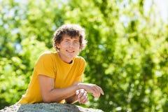 Un hombre rizado joven en un bosque imagenes de archivo