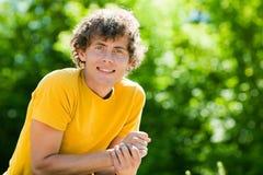 Un hombre rizado joven en un bosque fotos de archivo libres de regalías