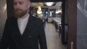 Un hombre rubio barbudo hermoso en la chaqueta abre las puertas de cristal de desplazamiento e incorpora el cierre del sitio para almacen de video