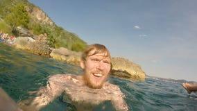 Un hombre saca en un goprote que se coloca en las rocas y que mira el mar la gente en el fondo está descansando claro almacen de metraje de vídeo