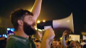 Un hombre salta con un altavoz en una ciudad de la noche y conduce una huelga almacen de video