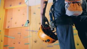 Un hombre se coloca cerca de una pared que sube con el casco de protección en manos, opinión de la parte posterior metrajes