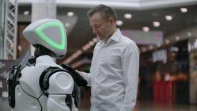 Un hombre se coloca con un bot del robot y le hace preguntas y pide ayuda haciendo clic en la pantalla en el cuerpo del robot almacen de video