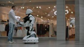 Un hombre se coloca con un bot del robot y le hace preguntas y pide ayuda haciendo clic en la pantalla en el cuerpo del robot metrajes