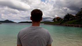Un hombre se coloca en la playa y las miradas en la bahía en el océano almacen de metraje de vídeo