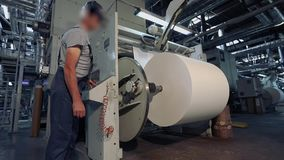 Un hombre se coloca en una fábrica para la producción de papel pintado Un hombre en la fábrica controla la máquina almacen de video